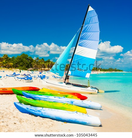 Colorful kayaks and sailing boats for rent at the beautiful beach of Varadero in Cuba - stock photo