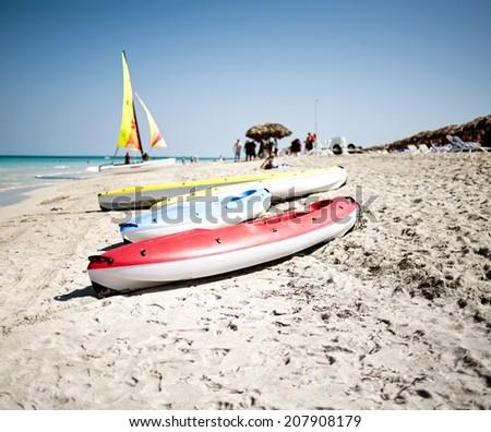 Colorful kayaks on a beach - stock photo