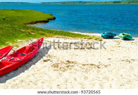 Colorful kayaks on a sandy beach with blue water and a green grassy shoreline in the background - stock photo