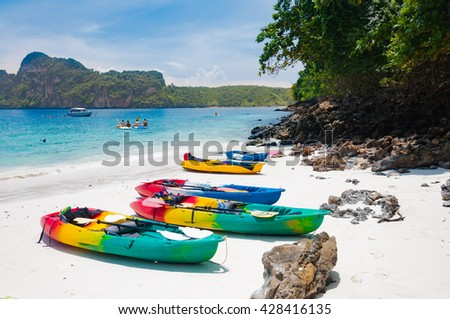Colorful kayaks on the beach with tourist behind and the boat - stock photo