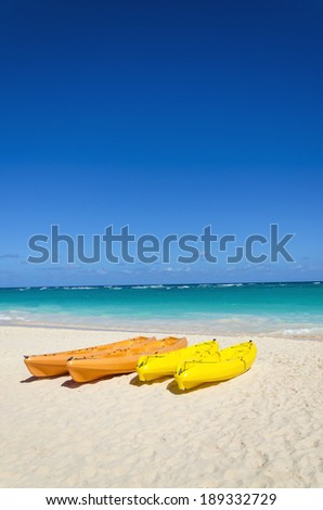 Colorful kayaks on the tropical sandy beach among lazur ocean and blue sky