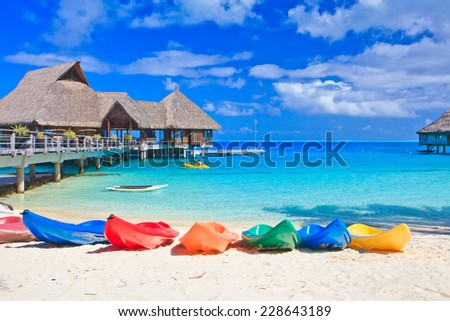 Colorful kayaks on white sand beach, Bora Bora, French Polynesia, South Pacific  Concept for relaxation, vacation, resort - stock photo
