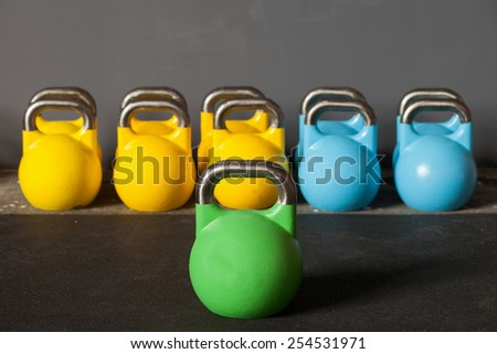 colorful kettlebells in a row in a gym - focus on the front kettle bell - stock photo
