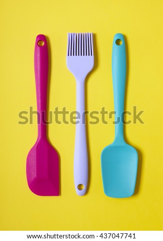 Colorful kitchen cooking utensils - a pink and blue baking spatula, and a purple pastry brush on a yellow background - stock photo