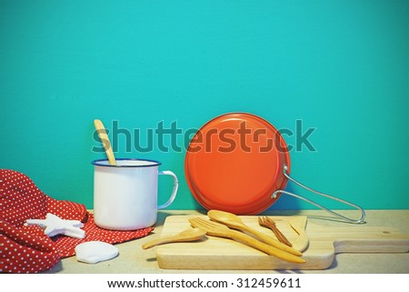 Colorful kitchen utensils and tablecloth on table front mint green background. Vintage effect. - stock photo