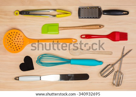 colorful kitchen utensils on wooden background - stock photo
