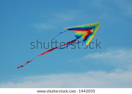 Colorful kite ascending over blue sky