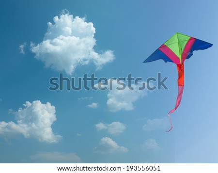 Colorful kite flying amidst fluffy clouds.