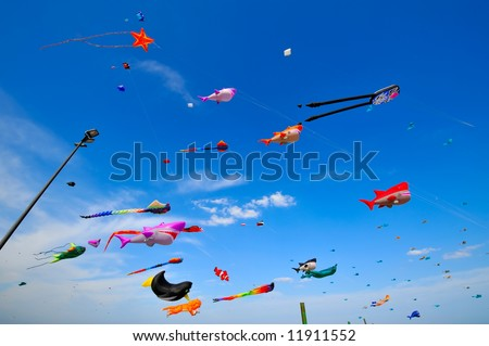 colorful kites flying in the sky during a festival - stock photo