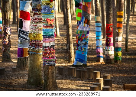 Colorful knitted trees in the park - stock photo