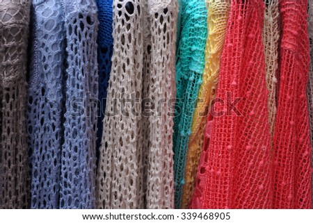 Colorful  lacy pullovers on hangers. Ladies' wear - stock photo