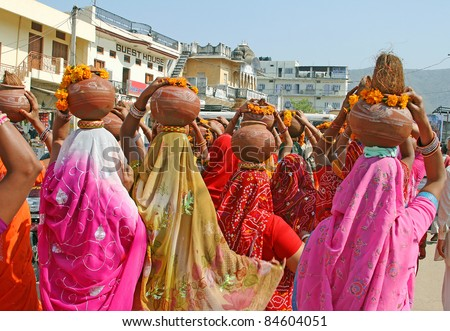 Colorful ladies with pots at Pushkar, India - stock photo