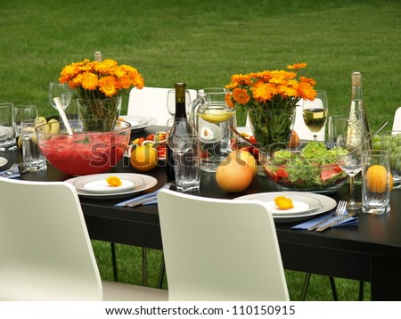 Colorful laid table in a beautiful garden - stock photo