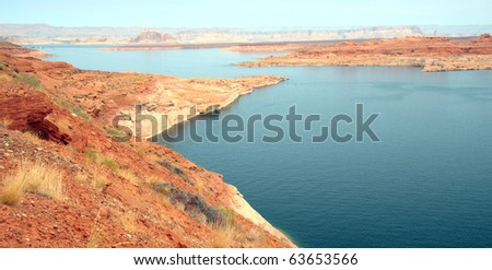 Colorful Lake Powell stretches over 180 miles and is populated with tall colorful orange, red, and white canyon walls, numerous islands and clean blue water - stock photo