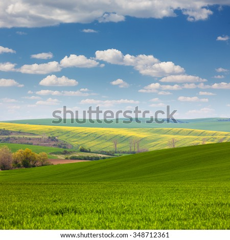 Colorful Landscape of fields in countryside - different colors of hills and blue sky - stock photo