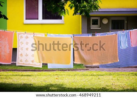 Colorful laundry, sheets and towels, hanging on line in front of residential house