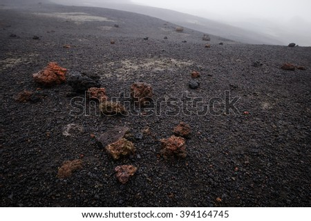 Colorful lava rocks on stony black ground on a foggy day on Fimmvorduhals, Iceland.