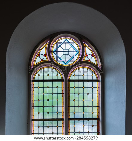 Colorful leaded glass window in a Dutch church from close. - stock photo