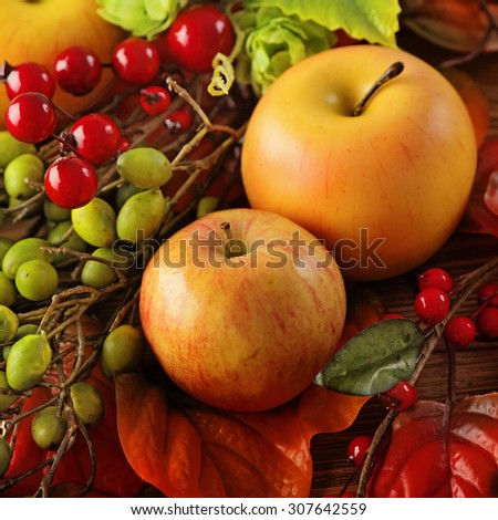 colorful leaves, apples and mushrooms on wooden background