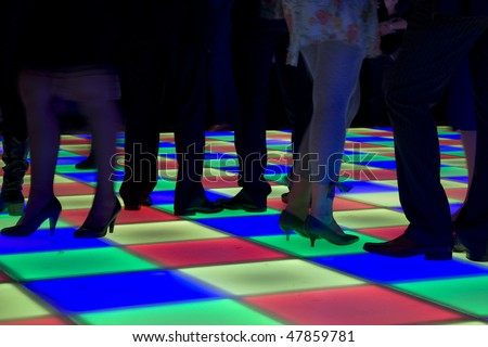 Colorful led dance floor with people dancing. - stock photo