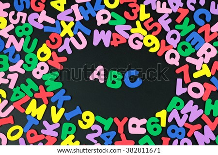 Colorful letters and numbers on black background. - stock photo