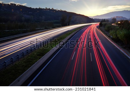 Colorful Light beams of moving vehicles on busy highway at dusk. - stock photo