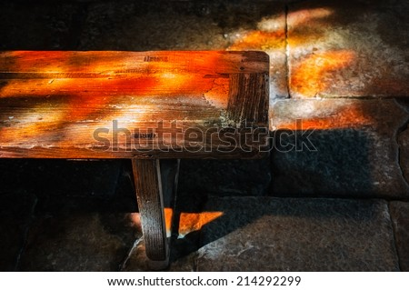 Colorful light spots on the wooden bench and stone brick floor in church. Sunlight filtered through the stained glass window. Selective focus on the bench.