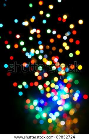 Colorful lights flying upwards on black background - stock photo