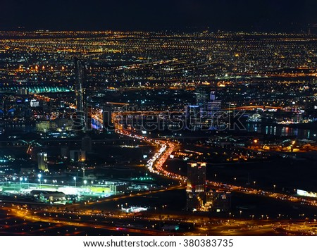 Colorful lights of Dubai aerial view. Illumination of residential districts and streets at night