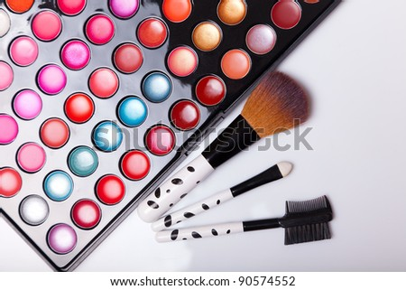 Colorful lip gloss palette with set of brushes, studio shot on white background - stock photo