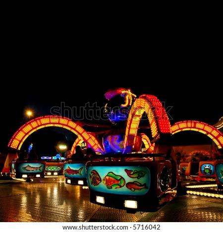 colorful lit octopus ride on a funfair at night - stock photo