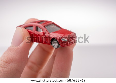 Colorful little toy car in hand on white background