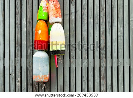 Colorful lobster buoys hanging on a weathered wooden fence. Copy space. - stock photo