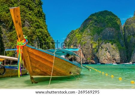 Colorful long tail boat at Maya Bay heavenly beach on a background of blue sky and azure sea and amazing limestone rocks, Phi Phi Islands, Thailand