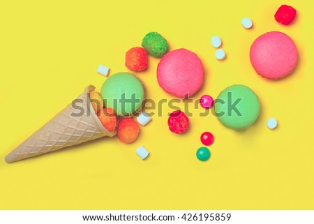 Colorful macaron or macaroon pink and green color drop out of ice cream cone of waffle with many small jelly candies and dragee with marshmallow on yellow background