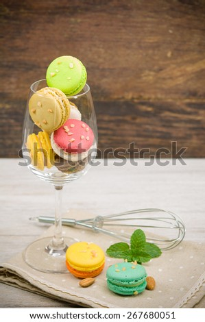 colorful macarons in wine glass on table. - stock photo