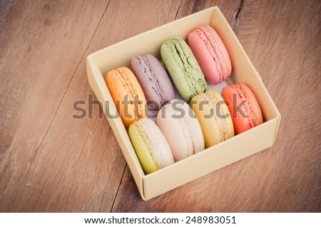 colorful macarons on a wooden floor - stock photo