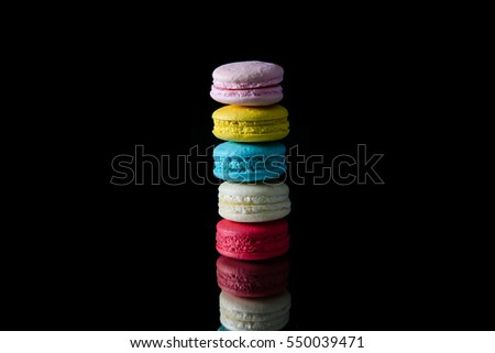 Colorful macarons on black background