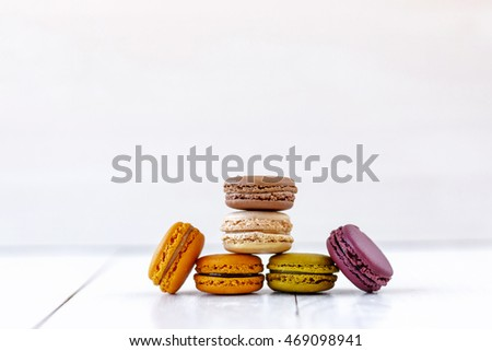 colorful macarons on white wood background