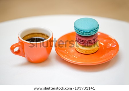 Colorful macarons with orange coffee cup - stock photo