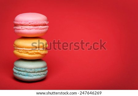 Colorful macaroon over red background - stock photo