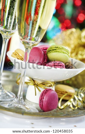 Colorful macaroons and Champagne on Christmass tree background - stock photo