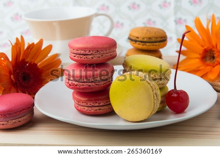 colorful macaroons and tea cup on sweet background
