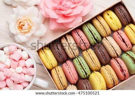 Colorful macaroons in a gift box and marshmallow in coffee cup on wooden table. Sweet macarons and flowers. Top view