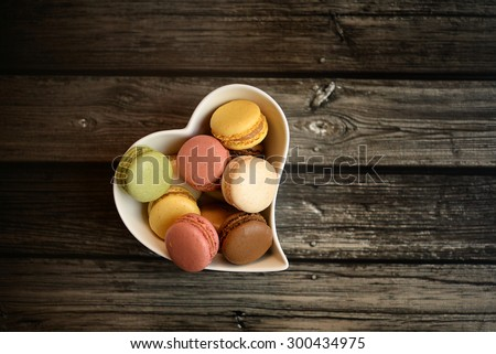 Colorful macaroons in a heart shaped white bowl on dark wood background