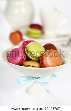Colorful macaroons in a white plate and fresh coffee - stock photo