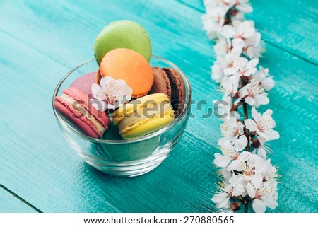 colorful macaroons in glass bowl with flower on wooden turquoise background - stock photo