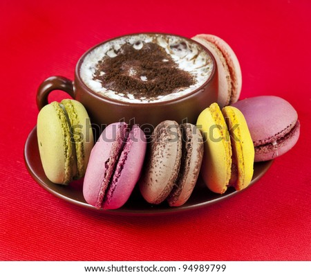 Colorful macaroons with coffee cup on a red background - stock photo