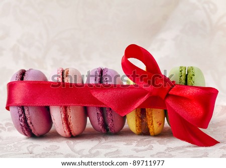 Colorful  macaroons with red ribbon bow  on  a  beige  napkin background - stock photo