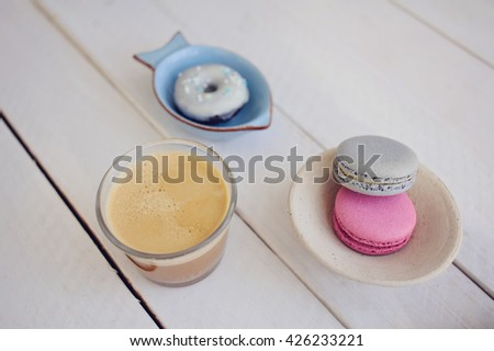 Colorful macrons in a plate and coffee cup over white wood. - stock photo